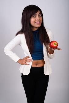 웃 고 빨간 사과 들고 서있는 젊은 행복 한 사업가 프리미엄 사진