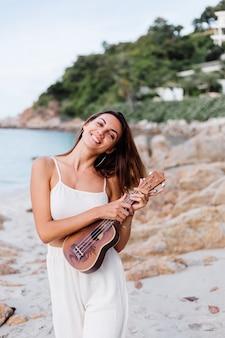 日没時の熱帯の岩のビーチでウクレレと若い幸せな穏やかな白人女性