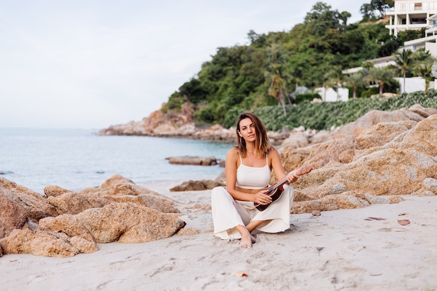 Young happy calm caucasian woman with ukulele on tropical rocky beach at sunset