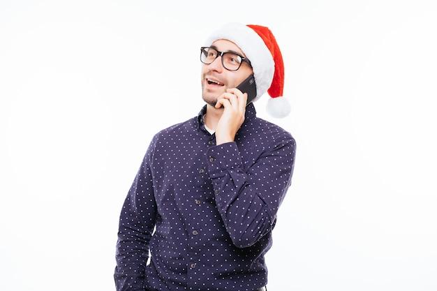 若い幸せなカジュアルな男が白い壁にサンタの帽子で電話で話します