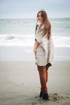 海のビーチ、秋の屋外でhikiing若い幸せなカジュアルな女性