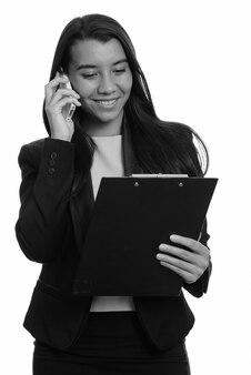 Молодой счастливый кавказский бизнесмен улыбается и разговаривает по мобильному телефону во время чтения в буфере обмена