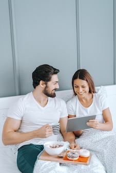 ベッドで朝食をとり、タブレットで動画を見て愛の若い幸せな白人カップル。