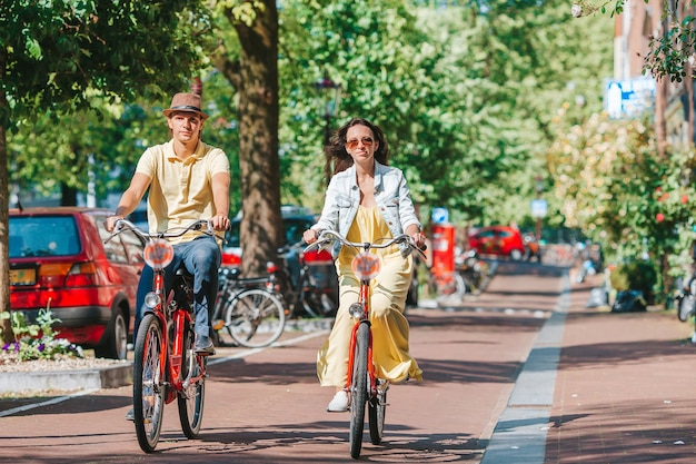 Молодая счастливая кавказская пара на велосипедах на старых улицах амстердама