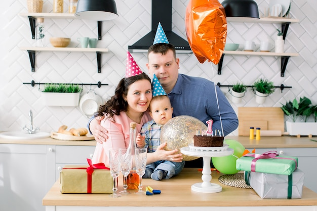 Young happy caucasian family celebrating a first birthday party of their little baby boy