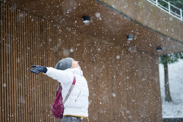 Молодая счастливая кавказская девушка с розовым рюкзаком, одетая в белую куртку, улыбается и наслаждается первым снегом с поднятыми руками