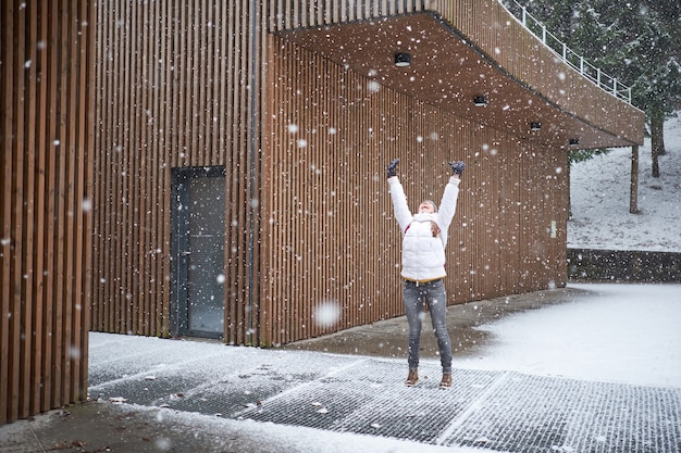Young happy caucasian girl with pink backpack dressed in white jacket smiling and enjoying first snow with rised hands