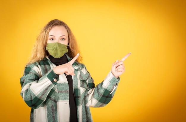 黄色の背景にコロナウイルス感染を防ぐために衛生的なマスクを身に着けているスペースをコピーするために指を上に向けて若い幸せな白人男性