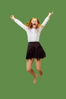 緑のスタジオの背景に分離された、空中でジャンプする若い幸せな白人の十代の少女。