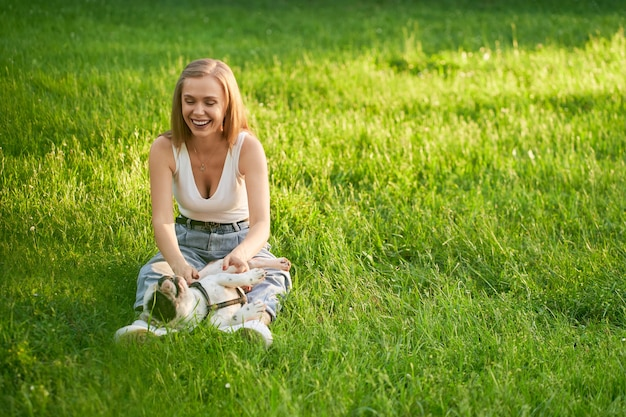 Young happy caucasian woman sitting on grass with male french bulldog on legs in city park. front view of stunning laughing girl enjoying summer sunset with pet, petting his belly.