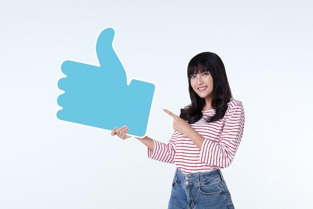 親指を立てるか、白のサインのような若い幸せな陽気なアジアの女性