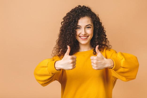 Молодая счастливая жизнерадостная курчавая женщина показывая большой палец руки вверх изолированный над бежевой предпосылкой.