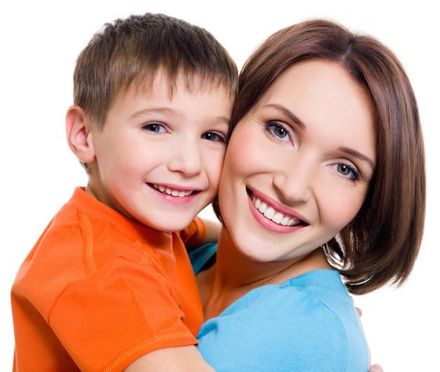 白い背景の上の幼い息子と若い幸せな陽気な母親