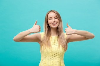Young happy cheerful woman showing thumb up over pastel blue background.