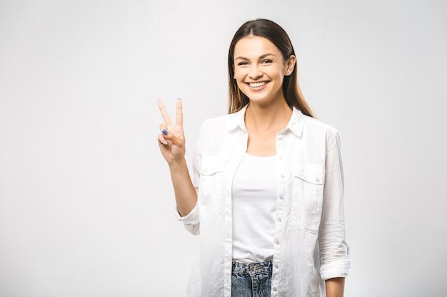 勝利の兆候を示す若い幸せな陽気な女性