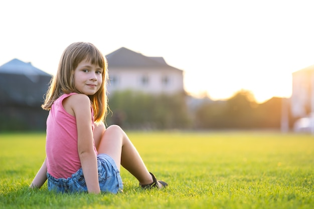 Young happy child girl resting while sitting on green grass lawn on warm summer day.