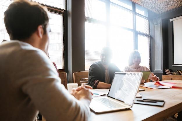 Giovani colleghi felici seduti in ufficio e coworking.