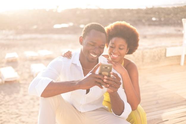 若い幸せなカップルアフリカ系アメリカ人のアフロレース多民族の人種の多様性は、光の明るい黄金の夕日の間に屋外のレジャー活動で電話とインターネットをお楽しみください。笑顔で滞在