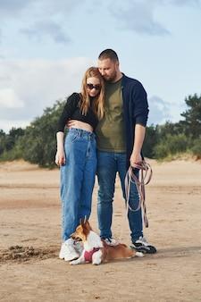 松や砂に対してビーチに立っている若い幸せなカップルと犬。