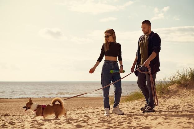 若い幸せなカップルとビーチを歩いている犬。離れている女性と男性
