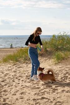 若い幸せなカップルと犬がビーチを歩いています。ひもにつないでコーギーの子犬と遊ぶ女性。