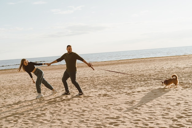 若い幸せなカップルとビーチの上を歩く犬。