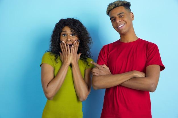 Giovane coppia felice in abiti casual in posa sulla parete blu
