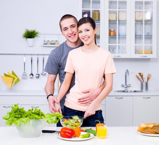 Giovani coppie felici che cucinano insieme nella cucina