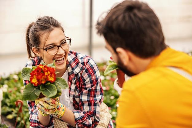 保育園で身をかがめると花のポットを保持している若い幸せなカップル。彼らは所有者です。