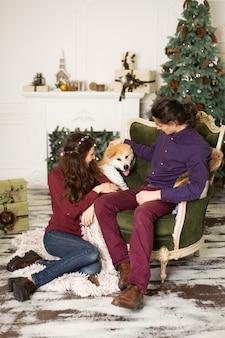 Молодая счастливая пара обнимает очаровательную собаку акита-ину, сидя на стильном ретро кресле