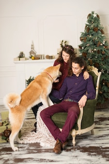 Young happy couple cuddling adorable akita inu dog while sit on stylish retro armchair for christmas holidays at home, christmas tree and fireplace , cozy home decorations