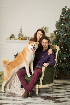 Young happy couple cuddling adorable akita inu dog while sit on stylish retro armchair for christmas holidays at home.