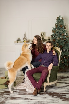 Young happy couple cuddling adorable akita inu dog while sit on stylish retro armchair for christmas holidays at home