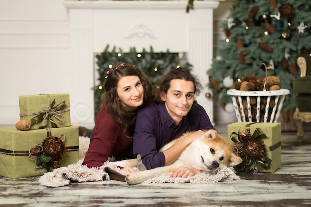 Young happy couple cuddling adorable akita inu dog with on the floor for christmas holidays at home.