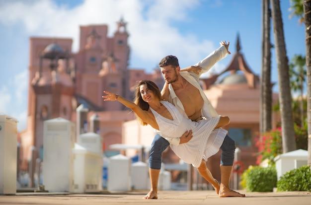 Молодая пара счастлива танцует в летнем парке.