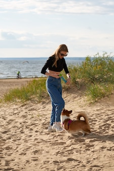 Young happy couple and dog walking along beach. woman playing with corgi puppy on leash.