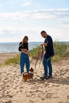 Young happy couple and dog walking along beach. woman playing with pet by toy.
