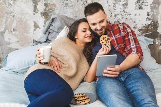 Молодая пара счастлива, пить кофе или чай в постели на утро. чтение новостей, использование планшета.