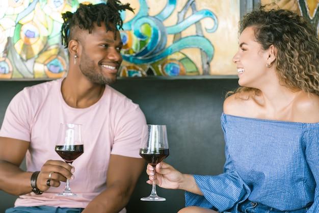 Giovani coppie felici che bevono una tazza di vino e si divertono insieme mentre hanno un appuntamento in un ristorante.