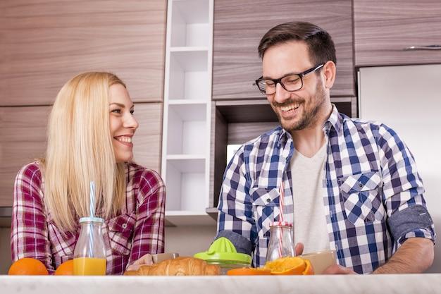 キッチンで新鮮なオレンジジュースを飲む若い幸せなカップル