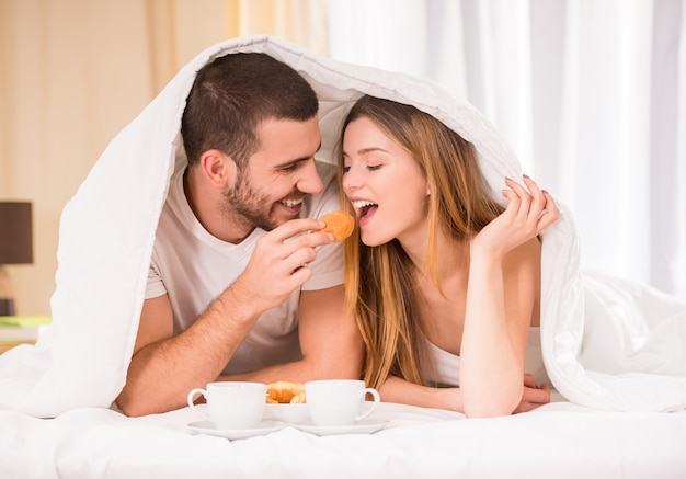 Young happy couple eating breakfast in her bedroom.