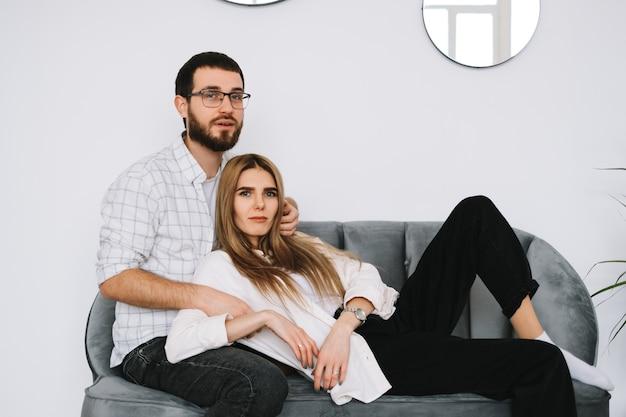 若い幸せなカップルは、自宅のソファで抱きしめて休んでいます。