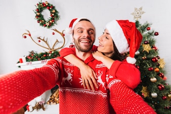 Young happy couple embracing near Christmas tree