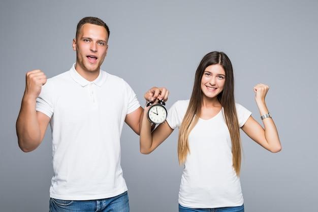 Молодая счастливая пара, полная энергии, держит будильник, одетые в белые футболки