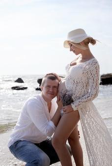 海の近くの若い幸せなカップルの将来の両親、男は腹の中で新しい生活を聞く