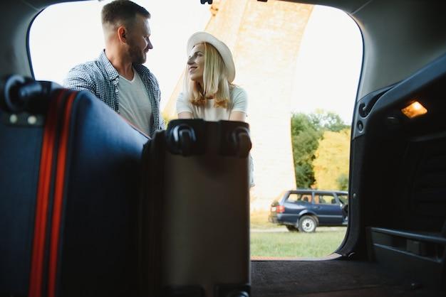 Молодая пара счастлива готовится к отпуску. положить чемоданы в багажник машины