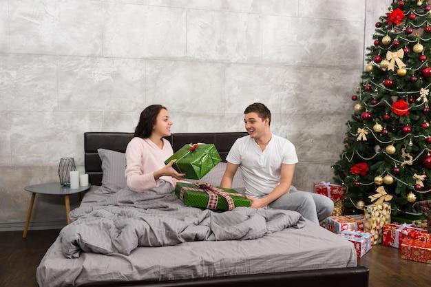 クリスマスの朝にロフトスタイルで寝室のベッドに座っている間、お互いにプレゼントを与える若い幸せなカップル