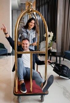 Молодая счастливая пара развлекается, толкая тележку для багажа в холле отеля