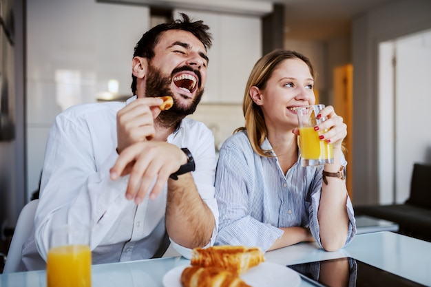 Young happy couple having breakfast at home.