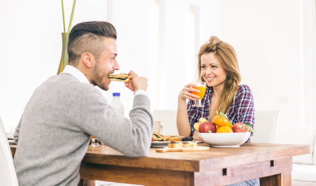 Young happy couple having breakfast in the morning